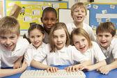 Crianças em idade escolar na mesma classe usando computadores — Foto Stock