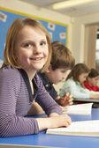 Schoolgirl Reading Book In Classroom — Stock Photo