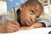 Unhappy Schoolboy Studying In Classroom — Stock Photo