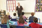 Dzieci w wieku szkolnym naukę w klasie z nauczycielem — Zdjęcie stockowe