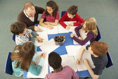 Crianças em idade escolar trabalhando juntos na mesa com o professor — Foto Stock