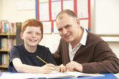 Mâle élève étudiant dans la salle de classe avec l'enseignant — Photo
