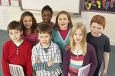 Retrato de crianças em idade escolar em pé na sala de aula — Foto Stock