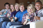 Group Of Teenage Friends Sitting On Sofa At Home Watching Drinki — Foto de Stock