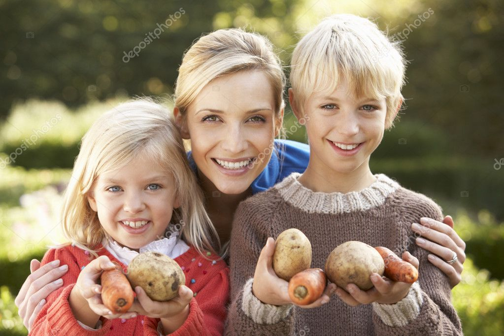 Young mother and children in garden pose with vegetables — Stock Photo #11879007