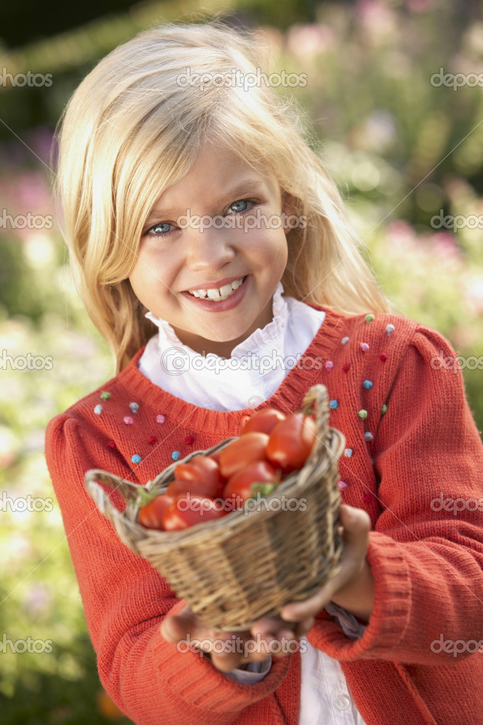 Young girl posing with tomatoes in garden — Stock Photo #11879014