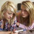 Two Teenage Girls Lying On Bed Looking At Pregnancy Testing Kit — ストック写真