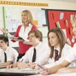 Teenage Students Studying In Classroom With Teacher — Stock Photo #11880173