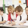 Teenage Students Studying In Classroom With Teacher — Stock Photo #11880174