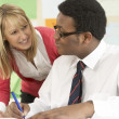 Teenage Student Working In Classroom With Teacher - Stock Photo