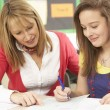 Female Teenage Student Studying In Classroom With Teacher — ストック写真