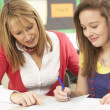 Female Teenage Student Studying In Classroom With Teacher - Stock Photo
