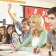 Teenage Students Studying In Classroom Answering Question — Stock Photo #11880312