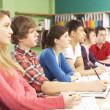 Teenage Students Studying In Classroom - Stock Photo