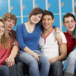 Teenage Students Relaxing By Lockers In School - Stock Photo