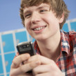 Male Teenage Student Using Mobile Phone By Lockers In School — Stock Photo