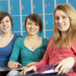 Female Teenage Students Relaxing By Lockers In School - Stock Photo