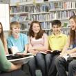 tonåriga elever i biblioteket läsa böcker med handledare — Stockfoto #11880432