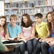 Stock Photo: Teenage Students In Library Reading Books With Tutor