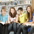 Teenage Students In Library Reading Books - Foto de Stock