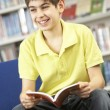 Male Teenage Student In Library Reading Book — Stock Photo