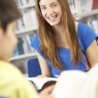 Female Teenage Student In Library Reading Book — Stock Photo