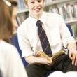 Male Teenage Student In Library Reading Book - Zdjęcie stockowe