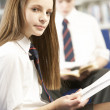 Female Teenage Student In Library Reading Book - Stockfoto
