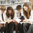 Teenage Students In Library Reading Books - Photo