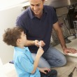 Son Helping Father To Mend Sink In Kitchen - Stock Photo