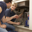 Plumber Teaching Apprentice To Fix Kitchen Sink In Home — Stockfoto
