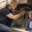 Female Plumber Working On Sink In Kitchen — Foto de Stock