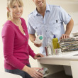 Couple Recyling Waste At Home - Stock Photo
