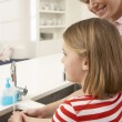 Mother And Daughter Washing Hands At Kitchen Sink - Foto de Stock