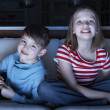 Children Watching TV Together Sitting On Sofa — Stock Photo