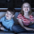 Stock Photo: Children Watching TV Together Sitting On Sofa