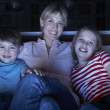Mother And Children Watching Programme On TV Sitting On Sofa Tog — Stock Photo #11880818