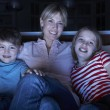 Mother And Children Watching Programme On TV Sitting On Sofa Tog — Stock Photo