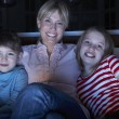 Stock Photo: Mother And Children Watching Programme On TV Sitting On SofTog