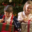 Children Opening Christmas Present In Front Of Tree — 图库照片
