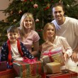 Family Opening Christmas Present In Front Of Tree — Stockfoto