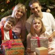 Family Opening Christmas Present In Front Of Tree — Photo