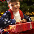 Young Boy Opening Christmas Present In Front Of Tree — Stock Photo
