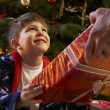 Young Boy Receiving Christmas Present In Front Of Tree — ストック写真