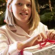 Young Girl Opening Christmas Present In Front Of Tree — Foto Stock