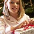 Young Girl Opening Christmas Present In Front Of Tree — ストック写真