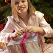 Young Girl Opening Christmas Present In Front Of Tree - Foto Stock