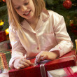 Young Girl Opening Christmas Present In Front Of Tree — Stock Photo
