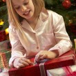 Young Girl Opening Christmas Present In Front Of Tree — Stok fotoğraf