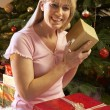 Woman Opening Christmas Present In Front Of Tree — Stock Photo